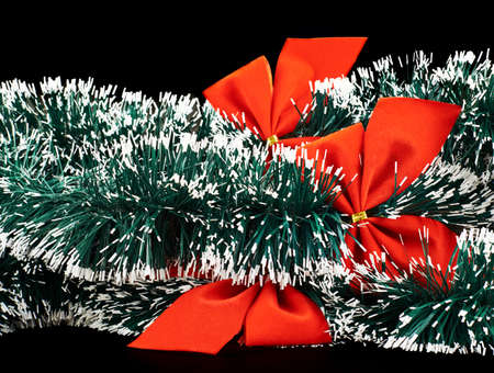 Seasonal Christmas decoration background as an xmas tree garland fragment covered with decorational red bows photo