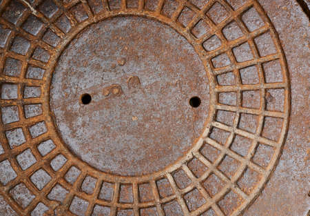Metal sewer manhole cover fragment as a background photo
