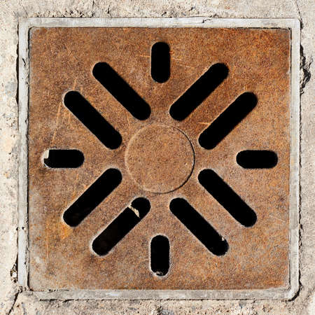Rusty drain grate in concrete floor as abstract background composition photo