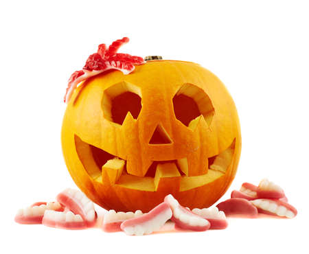 Jack-o-lanterns pumpkin with a spider and teeth shaped sweets around it, isolated over white background Stock Photo