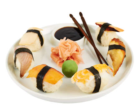 Nigirizushi sushi with a soy sauce, ginger, wasabi and chopsticks on a special ceramic plate isolated over white  Stock Photo