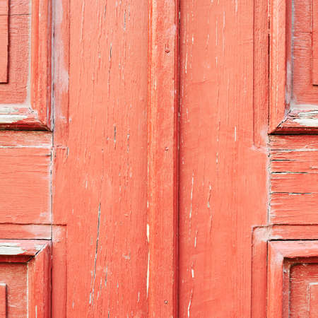 Old red painted wooden door fragment as abstract background composition photo