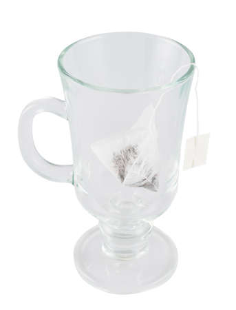 Glass teacup with a tea bag inside isolated over white  photo