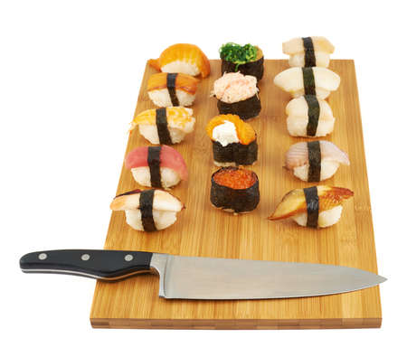 Making nigirizushi sushi over a wooden cutting board next to a cooks knife, composition isolated over white background photo