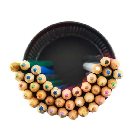 Black pencil holder full of colorful pencils, top view above, isolated over white background photo