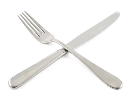 Crossed steel fork and kitchen knife composition isolated over white  photo