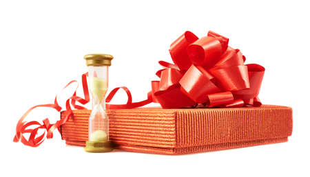 Sandglass and red gift box with a bow composition isolated over white background photo