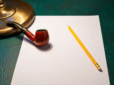 Writers desk composition as a copyspace empty sheet of paper, pencil and smoking pipe next to a table lamp photo
