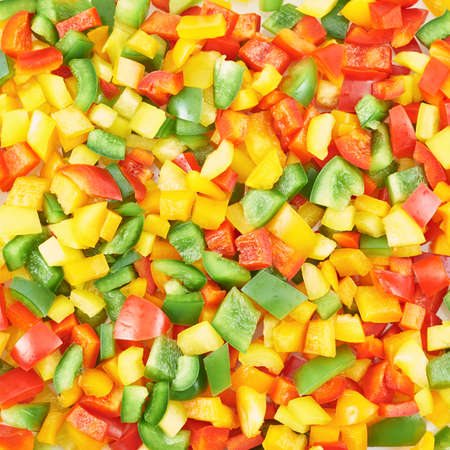 Surface coated with a sweet bell pepper cut into colorful pieces composition as an abstract food background photo