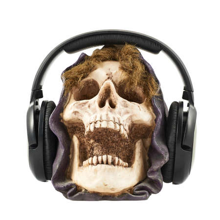 Horrible music concept as a headphones put on a ceramic skull head composition, isolated over white background Stock Photo - 24564195
