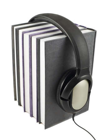 Audio-books concept composition as a stack of books with a headphones on it, isolated over white background photo