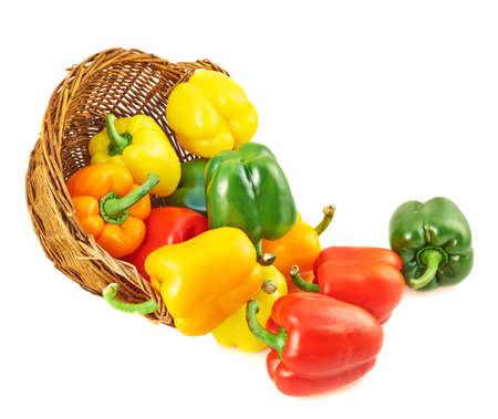 Wicker basket full of sweet green, yellow and red bell peppers isolated over white photo