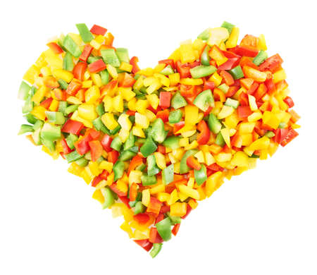 Heart shaped composition of sliced colorful sweet bell peppers isolated over a white background photo