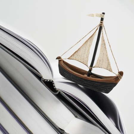 Erwerb von Kenntnissen Konzept als kleines Boot über einem geöffneten Buch-Seite-Zusammensetzung