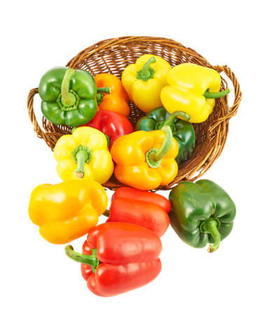 Wicker basket full of sweet green, yellow and red bell peppers isolated over white background photo
