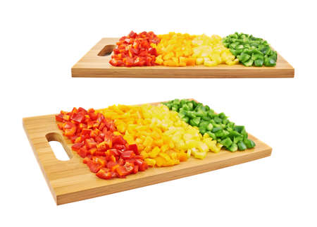 Sweet red, orange, yellow and green bell pepper cut in pieces over a wooden cutting board, isolated on a white background, set of two foreshortenings photo