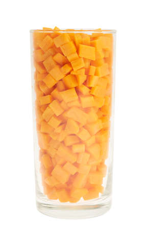 Tall glass full of carrot pieces isolated over white background photo