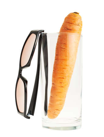 Glasses next to a carrot in a tall glass isolated over white background photo