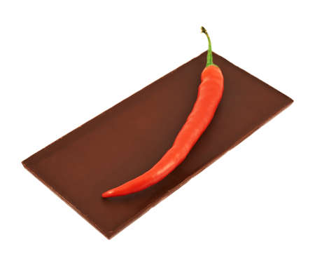 Red chili pepper over chocolate bar isolated over white  photo