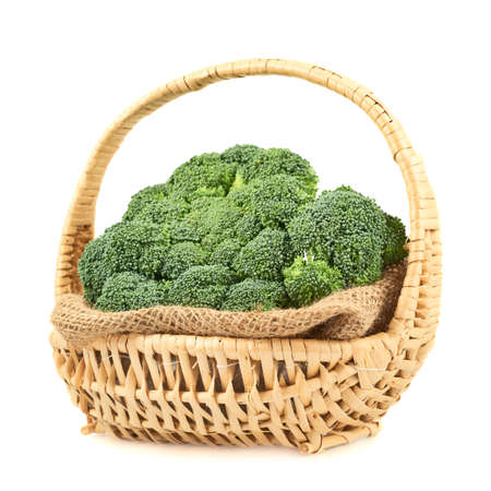 Green broccoli in a wicker basket isolated over a white background