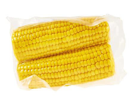 Two cornstick corn on the cob in a plastic vacuum packaging isolated over white background