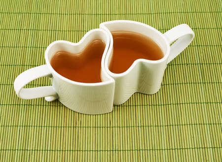Two heart shaped cups filled with tea over the green mat photo