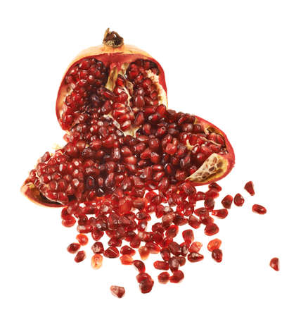 Opened pomegranate fruit with its seed lying around, isolated over white background photo