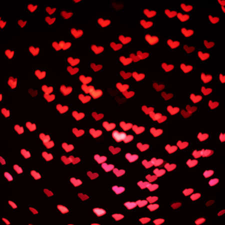 compostion: Red heart shaped bokeh over black foreground as an abstract background compostion Stock Photo
