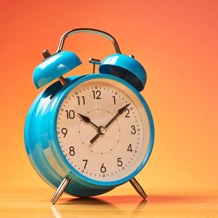 despertador: Reloj de alarma azul en la superficie de madera contra el fondo naranja