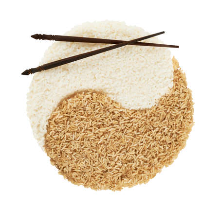 Yin yang sign made of white and brown rice with the eating sticks over it forming a smiley face, composition isolated over the white background photo