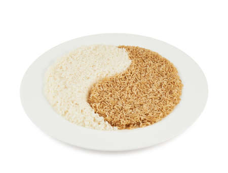 Plate of brown and white rice forming a yin yang sign isolated over the white background photo