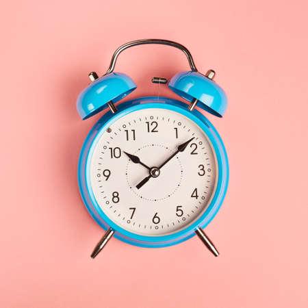ten empty: Bright blue alarm clock lying on pink surface