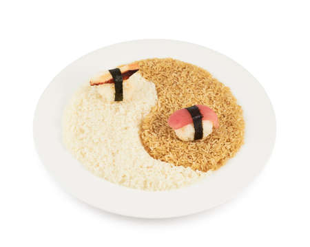 Plate of brown and white rice forming a yin yang sign with sushi over it, isolated over the white background photo