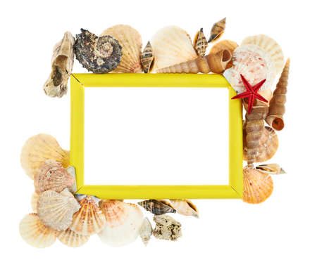 Empty copyspace picture wooden yellow frame decorated with seashells isolated over the white background photo