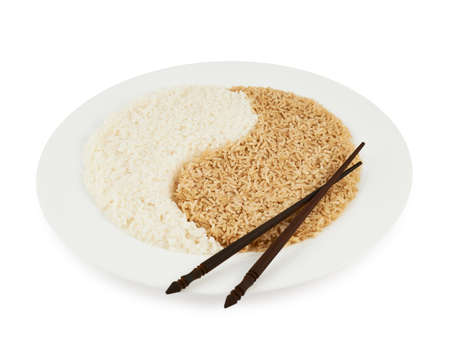 Plate of brown and white rice forming a yin yang sign with the eating sticks lying on top of it, isolated over the white background photo