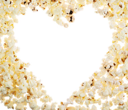 Heart shaped frame made of popcorn over the white background
