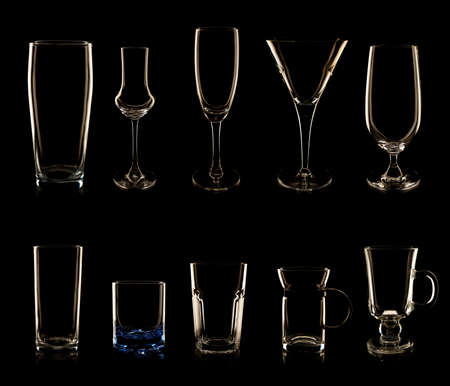 Set of multiple glasses and bottles shot in low-key lighting isolated over the black background