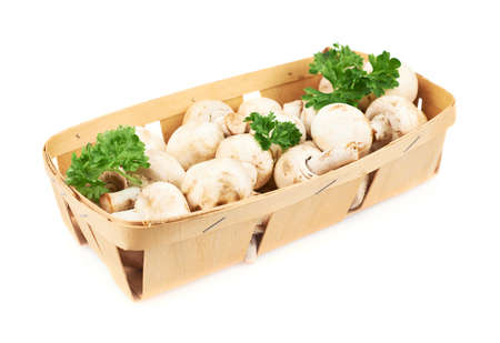 Champignon mushrooms and greens in a wooden box isolated over the white background photo