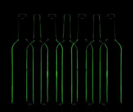 Abstract green glass bottles composition in a low-key illumination photo