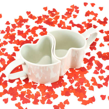 Two hearts shaped ceramic cups composition among red heart confetti over the white background photo