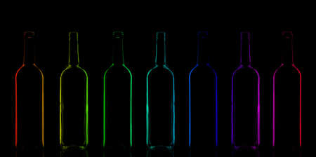 Row of rainbow colored bottles composition in a low-key lighting photo