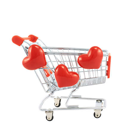 Shopping cart covered with the red hearts isolated over the white background photo