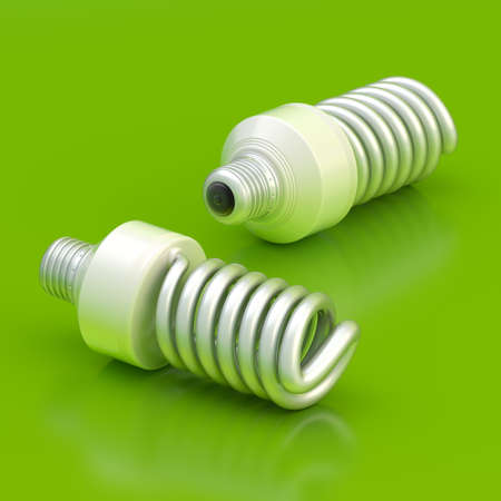 compact fluorescent lightbulb: Two energy saving bulbs lying over the green reflective surface Stock Photo