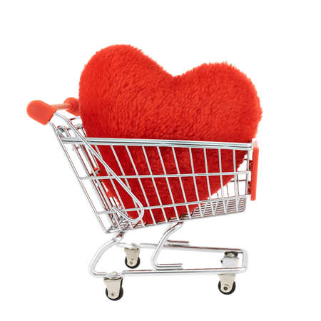 Plush red toy heart in a shopping cart isolated over the white background photo