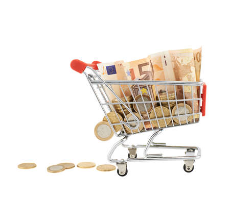 Shopping cart full of euro notes and coins, isolated over the white background photo