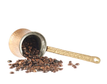 Copper cezve lying on its side and filled with coffee beans composition, isolated photo