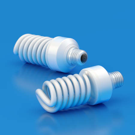 compact fluorescent lightbulb: Two energy saving bulbs lying over the blue reflective surface