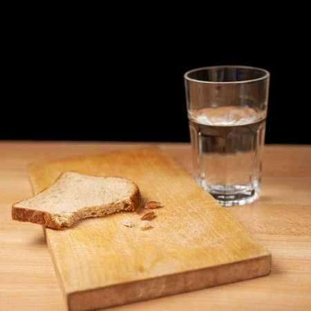 Glass of water and bread composition over the wooden surface photo