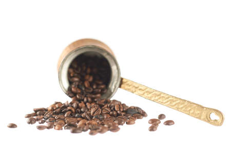 Copper cezve lying on its side and filled with coffee beans composition, isolated over the white background photo
