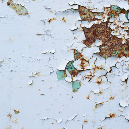 flaking: Blue paint flakes falling off the rusty metal surface as a background texture Stock Photo